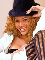 T-girl wears a curly wig and a hat for a star look